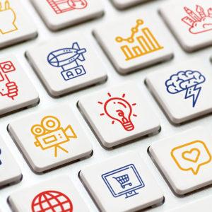 Colorful digital marketing icons on white keyboard