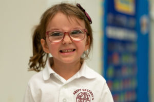 Cute young girl smiling with glasses and a private school uniform