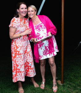 Two women in colorful, floral print sundresses attending an annual fundraising event for a prestigious private school in Albany, NY