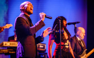 Two singers and a band in black-tie attire, performing for the Regeneron annual conference