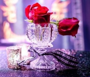 Small rose centerpieces with a sparkly table cloth as decorations for a corporate event
