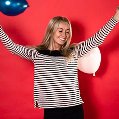 A blonde woman wearing a striped shirt throwing balloons in the air