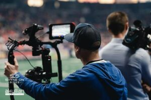 Behind the scenes of video producers filming b-roll for football highlights