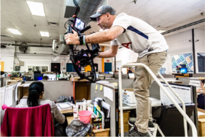 A video producer holding a gimbal and standing on a ladder to get the perfect b-roll shots