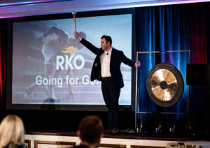 A business man on a stage about to ring a gong at a sales conference event