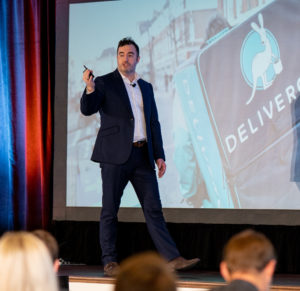 A business man giving a presentation on stage at a sales conference