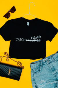 "Black ""Catch Flights Not Feelings"" crop top outfit on a yellow background"