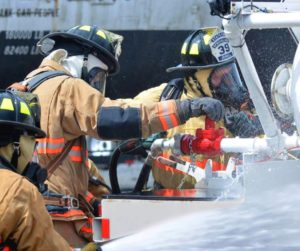 A group of firefighers using a hose to extinguish a fire