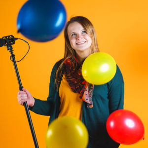 A graphic designer taking a creative headshot with colorful balloons against a yellow backdrop