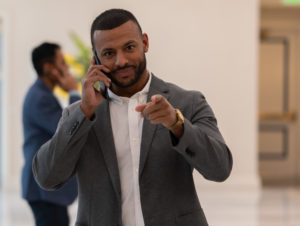 A business man on the phone and pointing at a camera