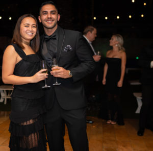 Two business professionals attending a black tie gala and holding champagne