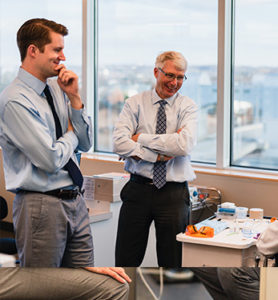 Two professional Orthodontists talking and laughing in an office