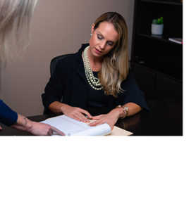 A business woman examining paper work at her desk while talking to a colleague