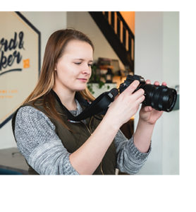 A young girl smiling while holding a Sony a7rii camera and shooting footage for a client testimonial