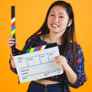 A girl in a floral print shirt holding a film clap board