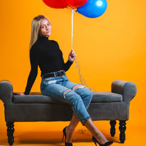 A young blonde woman in a black turtleneck holding colorful balloons