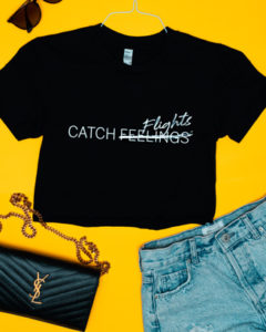 """Black """"Catch Flights Not Feelings"""" crop top outfit on a yellow background"""