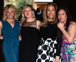 Four women in colorful dresses for a black tie gala event for Saint Gregory's Catholic School