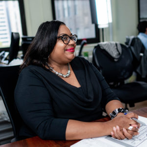 A business woman wearing glasses and pink lipstick, she is doing paperwork at a desk in Manhattan, New York