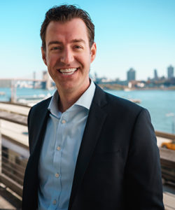 A business man in a suit smiling with the Manhattan skyline in the background