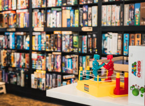 A wall of board games at a board game cafe in Albany, NY with Rock 'Em Sock 'Em Robots in the front