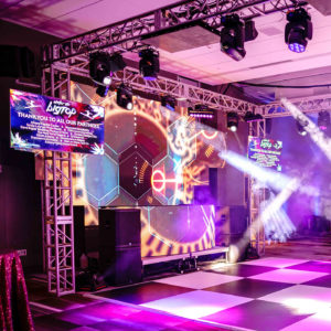 A dance floor and DJ booth at a corporate holiday party