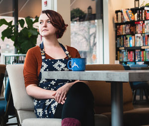 A woman wearing a patterned apron sitting in a coffee shop