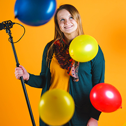 Our graphic designer Esther holding a camera pole with colorful balloons around her
