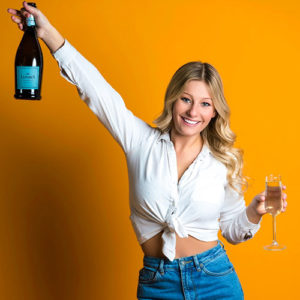 A young blonde woman holding champagne against a yellow background