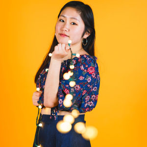 A girl in a floral print shirt and jean skirt holding Christmas string lights