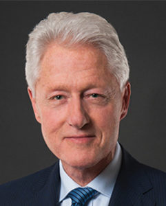Headshot of the former President Bill Clinton against a gray background
