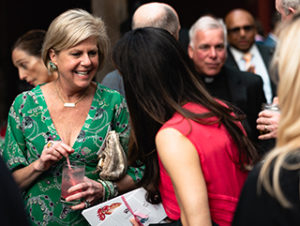 Two women at the annual Saint Gregory's fundraising gala, they are captured off-guard talking