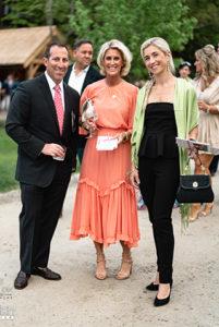 Three professionals, dressed to impress at fundraising gala for a prestigious Catholic school