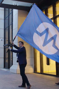 Business man and Chief Revenue Officer waving a large blue flag with the LogicMonitor logo for an Olympic-themed mockumentary video