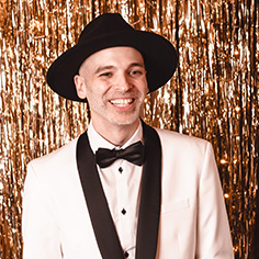 The founder of Akullian Creative, Rich Akullian, in a white suit and a black hat in front of a gold background