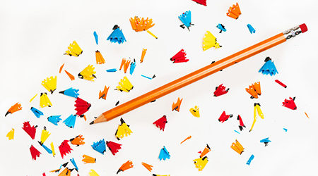 A pencil with colorful shavings around it, photo taken in-house at Akullian Creative