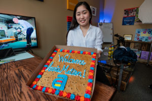 """A graphic designer and animator holding a cookie cake with her nickname """"Anne-mation"""""""