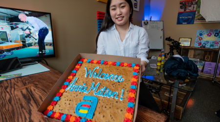 "A graphic designer and animator holding a cookie cake with her nickname ""Anne-mation"""