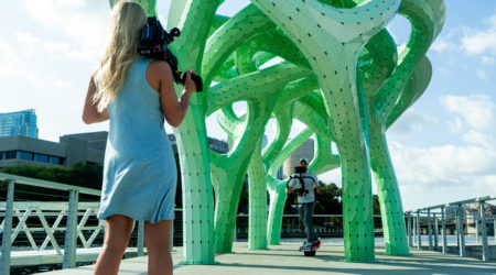 A blonde girl holding a Sony FS5 camera while a man films video with a gimbal in front of a sculpture in Tampa, FL