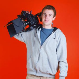 A video producer holding a Sony FS5 camera and smiling against a red background
