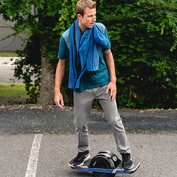 A man in a blue sweatshirt and khakis riding a Onewheel in a parking lot