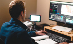 A video producer/filmmaker editing clips using Adobe Premiere Pro and Adobe After Effects