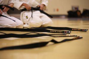 Karate students wearing black belts