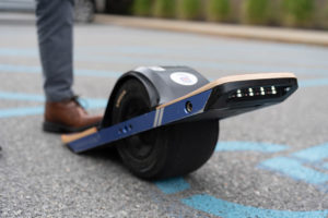 A close-up onewheel shot with Akullian Creative stickers on it in a parking lot