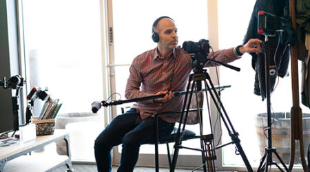 A camera man on set with a Sony a7rii camera, headset, and microphone