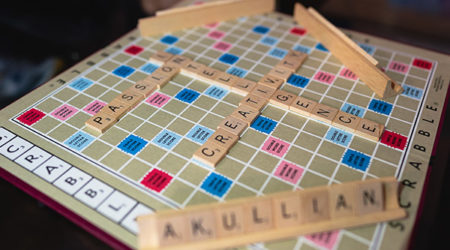 "A scrabble board with the words ""passion,"" ""intelligence,"" ""creativity,"" and ""Akullian"" written across it"