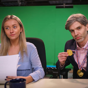 Two news reporters against a green screen recording video for a sales conference