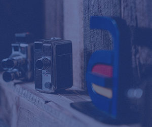 Old cameras and the Akullian Creative logo against a wooden background with a blue overlay