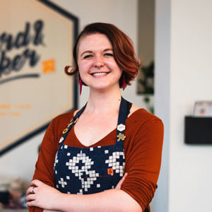 A local business owner, she is smiling and standing proud of pursuing her Board Game Cafe passion