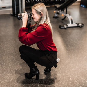 Girl crouching with a camera taking pictures inside a gym